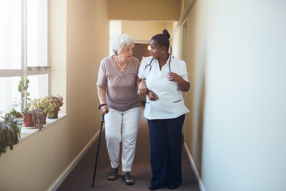 Elderly patient walking with a doctor