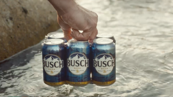 A man carrying a six-pack of Busch beer.