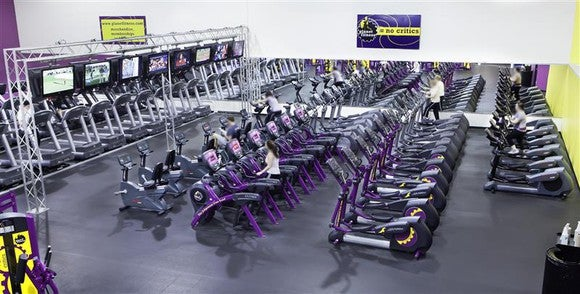 "A row of exercise equipment inside a Planet Fitness. The company's ""Judgement Free Zone"" statement is displayed on the wall."