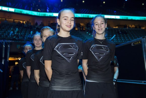 Ballkids at tennis tournament in batman versus superman themed Under Armour t-shirts.