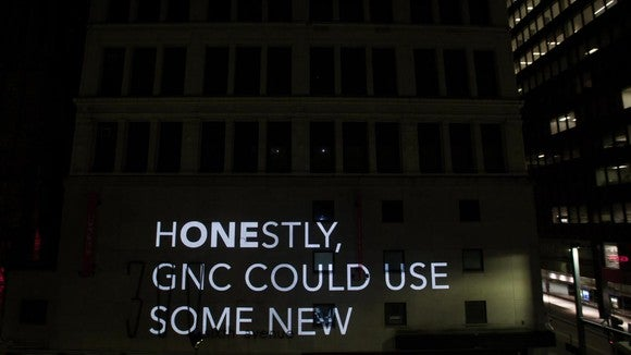 "Video image message projected on side of building, saying ""Honestly, GNC could use some new"""