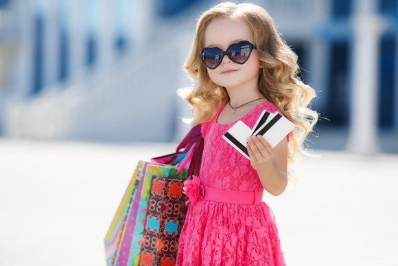 A girl in sunglasses clutches credit cards in her hand.