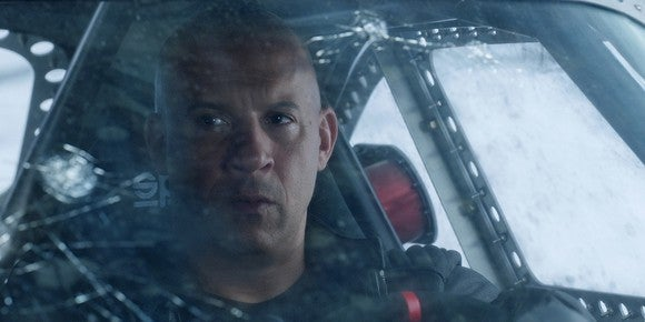"Actor Vin Diesel as ""Dom"" in ""Fate of the Furious"" driving a car with a cracked windshield."