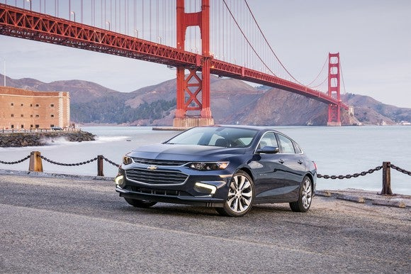 A Chevy Malibu is parked in front of the San Francisco Golden Gate Bridge