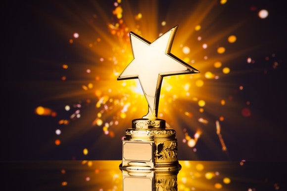 Gold star-shaped trophy against shiny sparks background emitted from sparkler