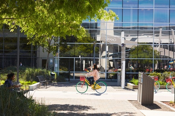 A person riding a bike in front of the Google campus.