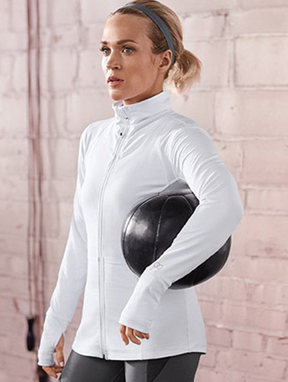 Carrie Underwood wearing a white sports jacket and holding an exercise ball.