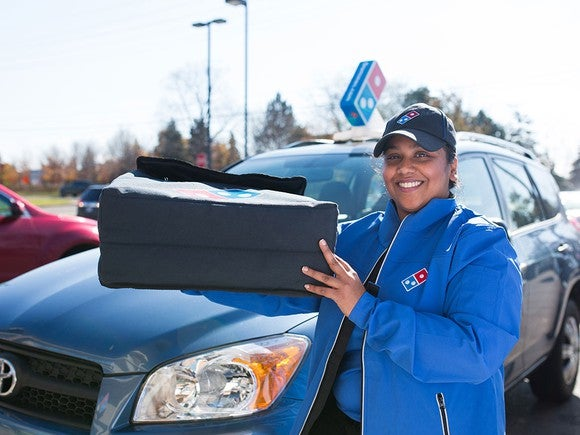 A Domino's delivery driver smiles next to her car, holding a bag of pizzas to go.