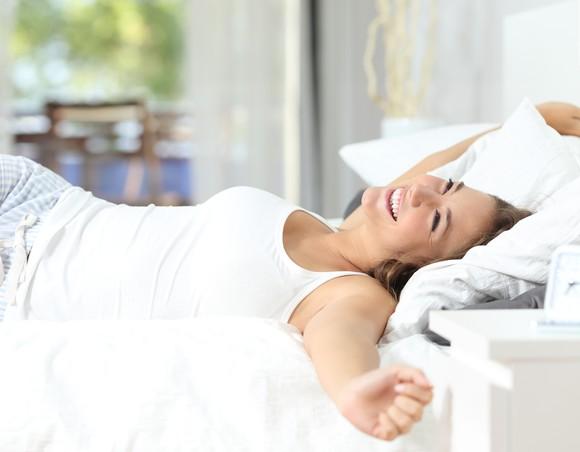 Woman waking up on a mattress.