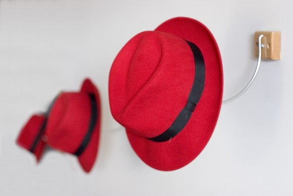 A line of red fedoras, hanging on wall hooks.