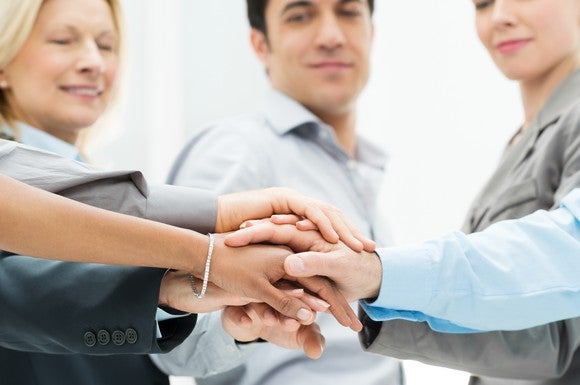 A team of business people putting their hands together to signify a partnership has been formed.