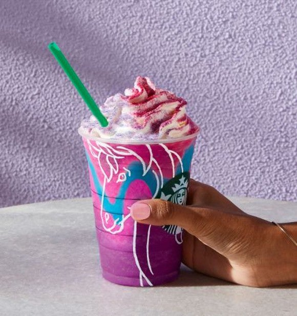 A hand holding a Unicorn Frappuccino
