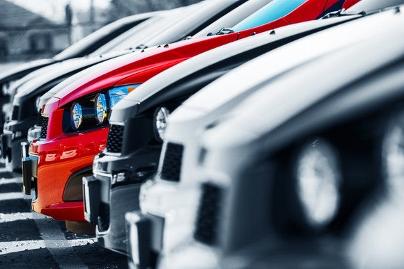 Profile view of the hoods of a row of cars at a dealership.