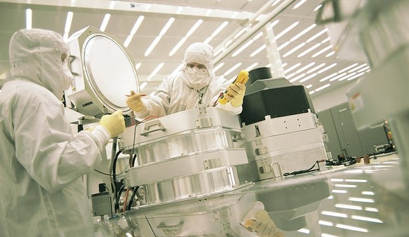 Two people working on semiconductor equipment.