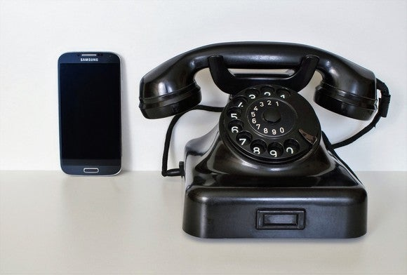 A rotary phone next to a modern smartphone.