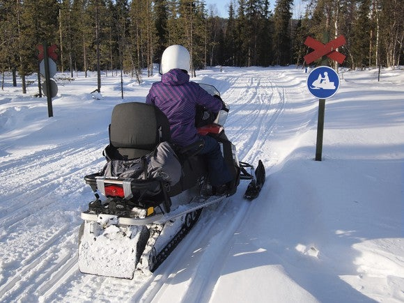Snowmobiler facing no snowmobiles sign.