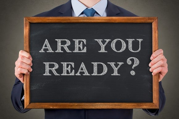 "Man in suit holding blackboard on which is written ""are you ready?"""