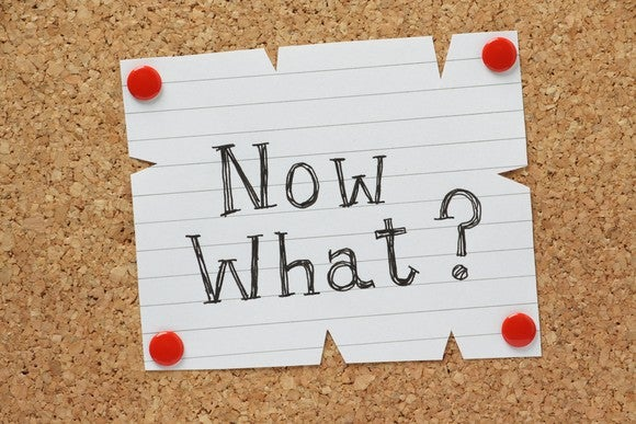 "Note that says ""Now what?"" tacked to a corkboard"