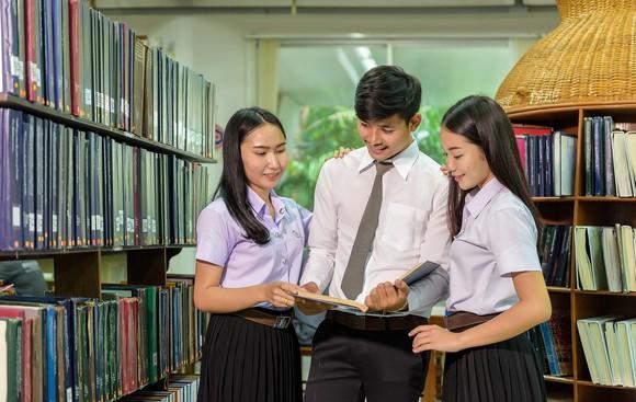 Three students looking at a book.