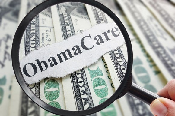 """Magnifying glass looking at word """"Obamacare"""" set against dollar bills"""