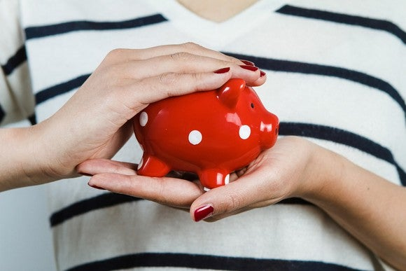 Woman holding red piggy bank.