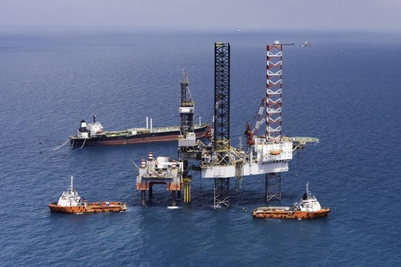 An offshore drilling rig surrounded by several support vessels.