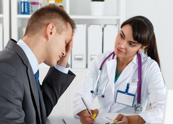 A patient with a migraine speaking to his doctor.