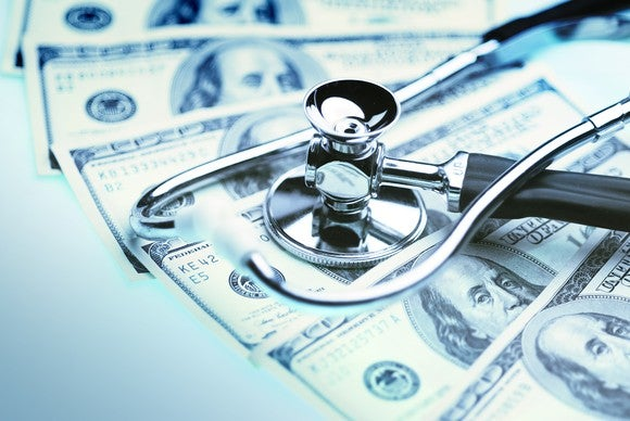 A stethoscope laying on a stack of cash.