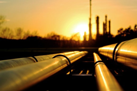 Pipelines leading to oil refinery at sunset.