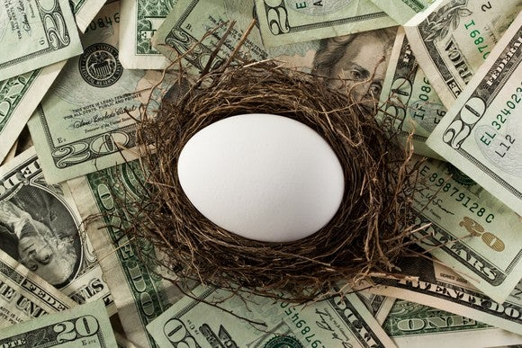A nest egg surrounded by U.S. dollar bills.