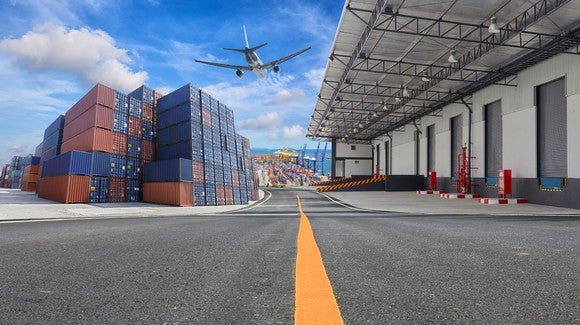 Cargo plane taking off from airport above a warehouse and stacked shipping containers.