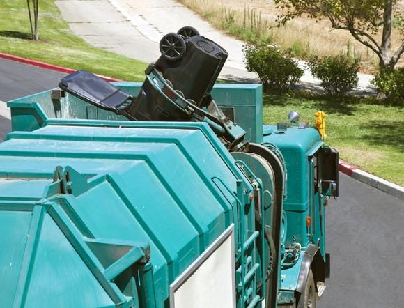 Robotic arm trash truck dumps a large black can.