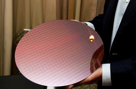 An Intel employee holding a wafer of seventh-gen Core chips.