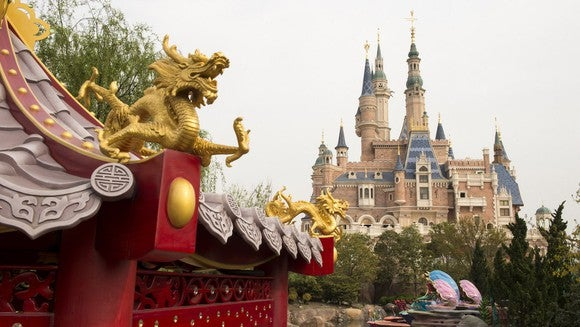 A dragon ornament adorns a building with Disney's castle in the background at Disney's new Shanghai park.