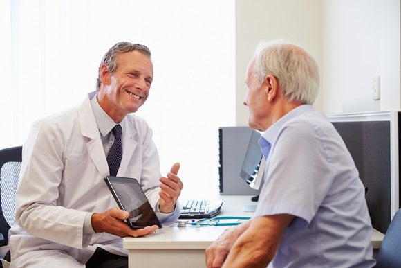 A doctor discussing Medicare options with an elderly patient.
