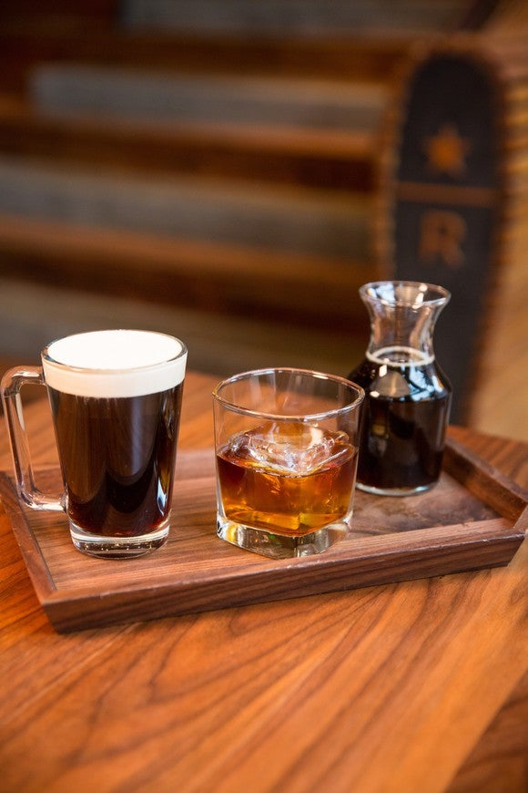 A cup of coffee on a wooden serving board.