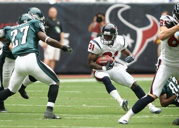 A Houston Texans running back tries to juke a Philadephia Eagles defender during an NFL game.
