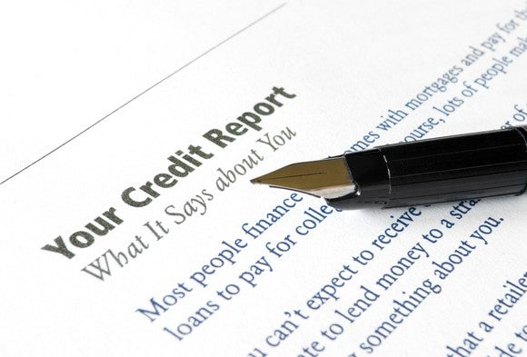 A pen pointing to the definition of what a credit report says about a consumer.