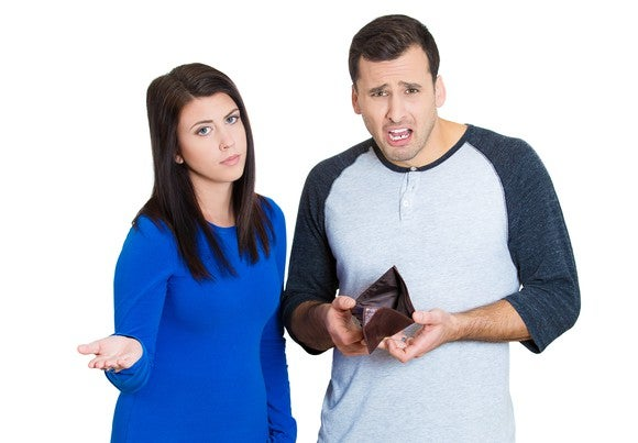 A young couple showcasing their empty wallet.