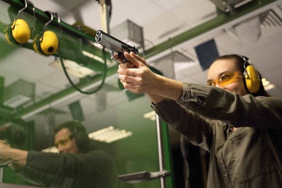 A woman takes target practice at a gun range.
