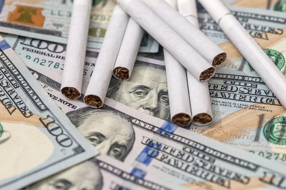 Cigarettes are scattered across a pile of $100 bills.