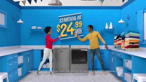 "A couple stands in front of rented appliances in front of a sign that says ""starting at $24.99 per week"""