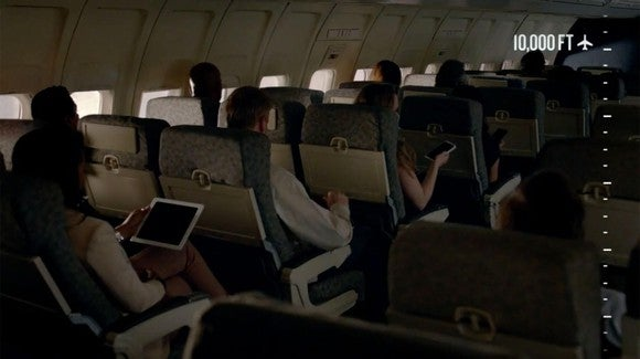 """A airplane cabin with various people connected to their devices and text saying """"10,000 feet"""""""
