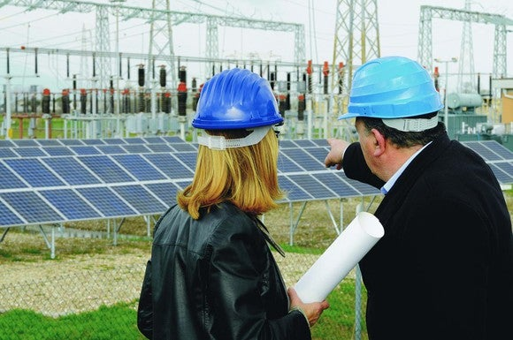 A man and woman in hardhats, overlooking a solar energy project.