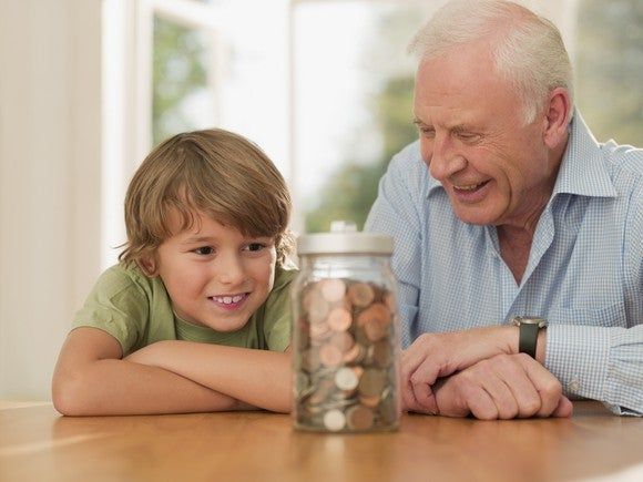 Grandfather and grandson looking at a jar of coins.