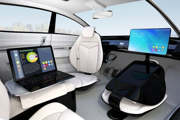 The inside of an autonomous vehicle, with a laptop and monitor set up for work.