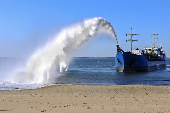 Dredging ship spraying sand onto shore.