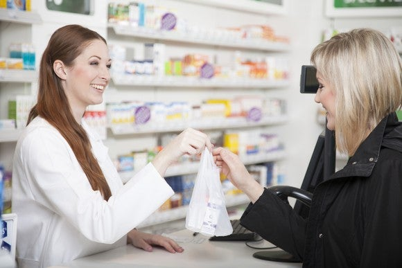 A pharmacist hands an order to a customer.