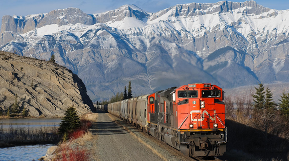 Canadian National train with snow-capped mountains in the distance