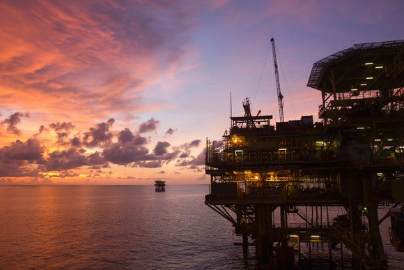 Oil production platform at sunset